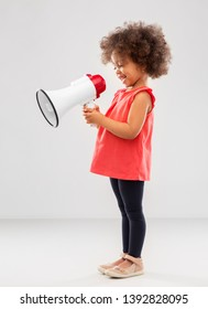 childhood and people concept - happy little african american girl with megaphone over grey background
