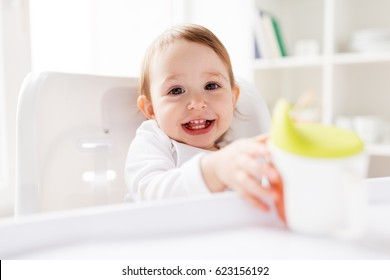 childhood and people concept - happy smiling little baby drinking from spout cup sitting in highchair at home