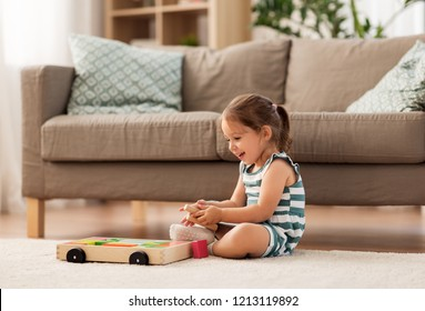 childhood and people concept - happy three years old baby girl playing with toy blocks at home