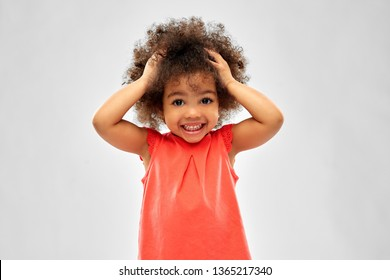 childhood and people concept - overwhelmed little african american girl holding to head over grey background