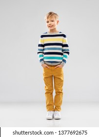 childhood and people concept - portrait of nice little boy in striped pullover over grey background