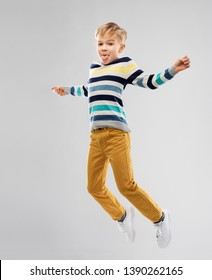 childhood and people concept - portrait of nice little boy in striped pullover jumping and having fun over grey background