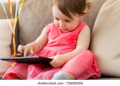 childhood, people and technology concept - happy baby girl with tablet pc computer at home