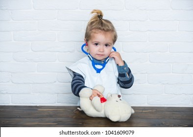 Childhood, playroom, nursery. Child play doctor with teddy bear on white wall. Game, development, imagination. Future profession concept. Baby veterinarian examine toy animal with stethoscope.