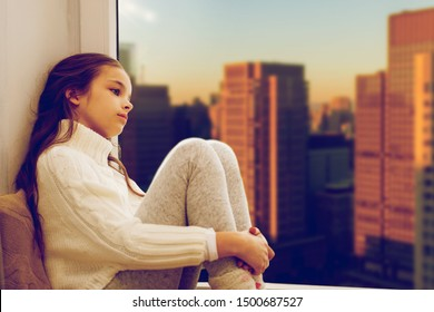 childhood, sadness and people concept - sad beautiful girl in sweater sitting on sill at home window over city skyscrapers background