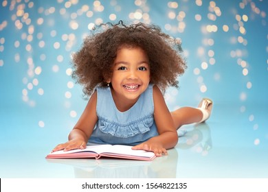 childhood, school and education concept - happy smiling little african american girl reading book over festive lights on blue background