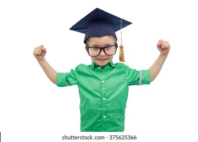 childhood, school, education, knowledge and people concept - happy boy in bachelor hat or mortarboard and eyeglasses showing strong hands