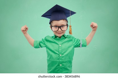 childhood, school, education, knowledge and people concept - happy boy in bachelor hat or mortarboard and eyeglasses showing strong hands over green school chalk board background
