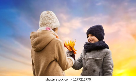 childhood, season and love concept - smiling little boy giving autumn maple leaves to girl over sky background