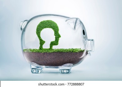 Childhood is the seed of adulthood. Grass growing in the shape of a cut out child head inside a man head, inside a transparent piggy bank, symbolising the care and investment needed in childhood.