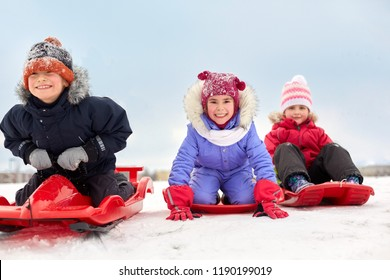 childhood, sledging and season concept - group of happy little kids sliding down on sleds in winter