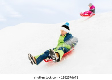 childhood, sledging and season concept - happy little kids sliding on sleds down snow hill in winter