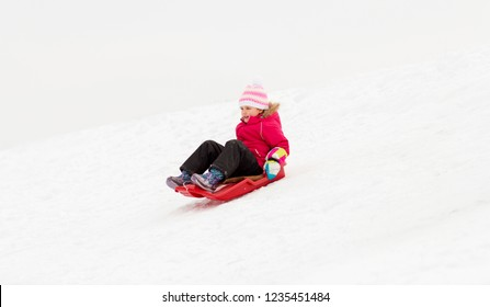 childhood, sledging and season concept - happy little girl sliding down on sled outdoors in winter