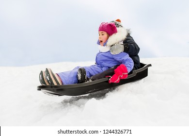 childhood, sledging and season concept - happy little kids sliding on sled down snow hill in winter