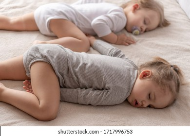 Childhood, sleep, relaxation, family, lifestyle concept - two young children 2 and 3 years old dressed in white and beige bodysuit sleep on a beige and white bed at lunch holding hands top view.