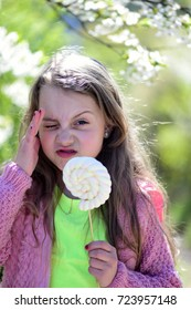 Childhood, sweets and natural beauty concept. Kid in pink sweater holds white lollipop. Girl with unsatisfied face on nature background, defocused. Schoolgirl with candy walks near blooming trees