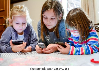 Childhood, technology and family concept - little girls with tablet and smartphones in the kitchen at home. The reflection of the phone on the girl's face - Image
