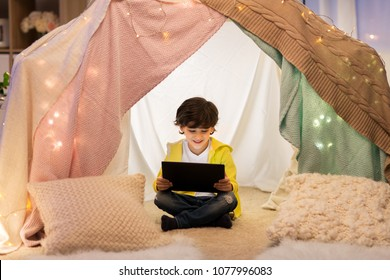 childhood, technology and hygge concept - happy little boy with tablet pc computer in kids tent at home