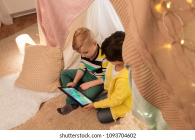 childhood, technology and hygge concept - happy little boys with tablet pc computer in kids tent at home