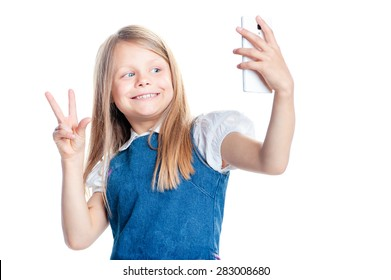 Childhood and technology. Pretty little girl taking selfie by her smartphone. Isolated on white.