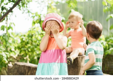 Childhood Three children of same age show different emotions. Kids in green garden play game deaf blind dumb outdoors in summer. sister and brothers show gesture, cover your face with your hands