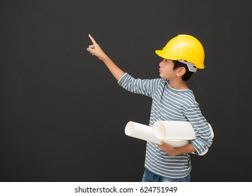 Childhood,Construction, architecture, building and people concept - smiling little boy in protective helmet holding a poster pointing finger,Picture of little boy architect in helmet showing direction