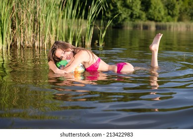 childish beauty: picture of glamor beautiful brunette young female in bikini having fun relaxing in water on green summer outdoors copy space background