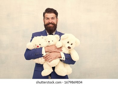 Childish excitement. Childish businessman cuddle soft toys. Bearded man dream of childhood. Childish adult. Happy and childish.