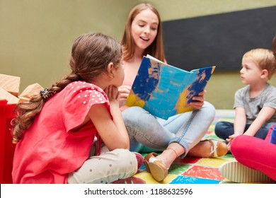 Childminder and children reading from a children's book in a kindergarten