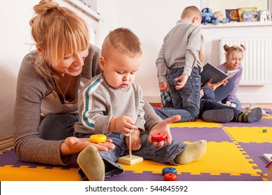 Childminder playing with a toddler while sitting on the flour