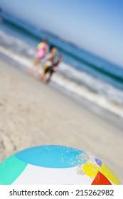 Children (6-10) standing on sandy beach near sea, focus on beach ball in foreground (tilt)