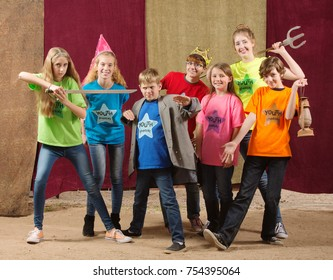 Children at acting camp pose together with swords and trident
