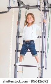 Children Activity Concepts. Portrait of Happy Caucasian Girl Having Physical Exercises on Wall Bars Indoors. Vertical Image Orientation
