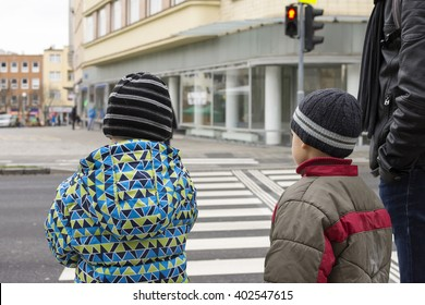 Children and adult waiting at pedestrian crossing for green light.
