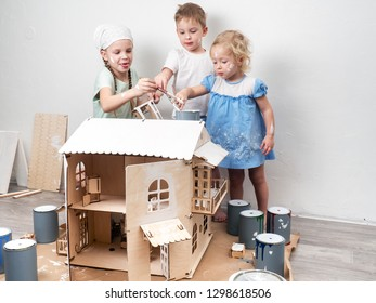 Children as adults: A boy and a girl paint a doll house white and get dirty with paint. Authentic photo.