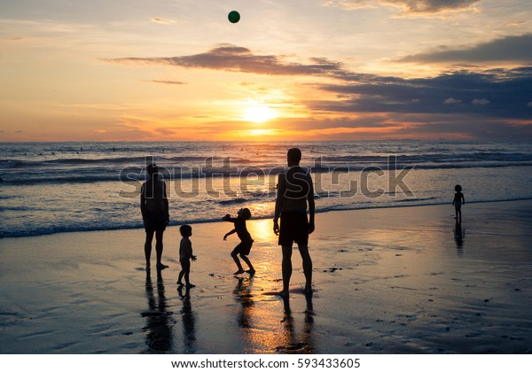 Children and adults play ball on the beach during sunset on the ocean background with floating surfers. Indonesia Bali