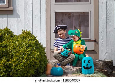 children after a trick or treating. pirate and dragon look at candy and party favors from Halloween bucket. Teal pumpkin.