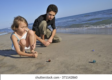 Children (aged 8 and age 14) playing marbles on beach, Provence, France, Europe