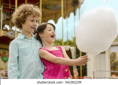 Children are amazed with the size of cotton candy. Two cute siblings look at the dessert with amazement, while little girl opened her mouth.