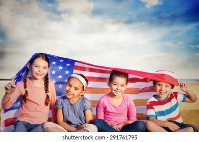 Children with american flag against serene beach landscape