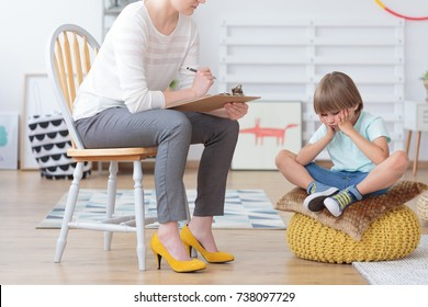 Children anxiety and depression concept, psychologist talking with sad little boy at the office