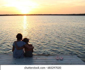 children with arms around each other sitting on the dock at sunset