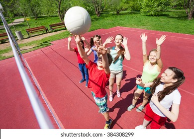 Children with arms up to ball play volleyball near the net on the court during sunny summer day outside