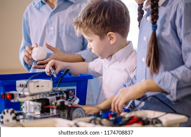 Children assambling robotic toy. Selective focus of adorable boy of 6-7 years old being busy with constructing electric robot with the help of older children. Communication and digital concept.