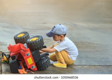Children attempt to maintenance his ATV toy by himself. Asian boy age 4 years old in white shirt want to repair the car and flipped vehicle. Background for kid's recreation or imagination learning
