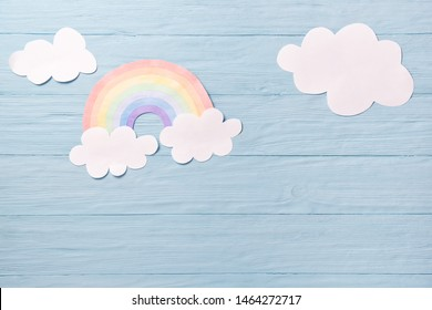 Children or baby background, white clouds with rainbow on the blue wooden background