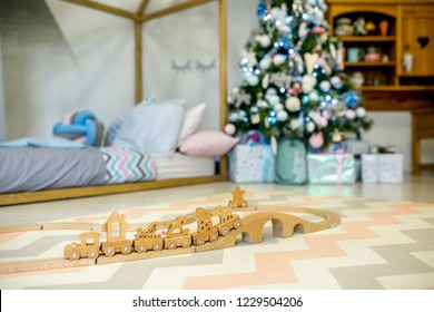 Children bedroom decorated for Christmas. Wooden toy railway on the background of the Christmas tree lights and bed. Christmas morning. Holiday mood