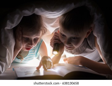 Children bedtime. Sister and brother are reading a book under a blanket with flashlight. Pretty young boy and lovely girl having fun in children room.