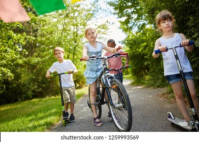 Children with bicycle and scooter driving together in the park in summer