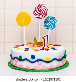 Children birthay cake with number one and colorful lollypops/ dessert for children's day celebration / 1st of june